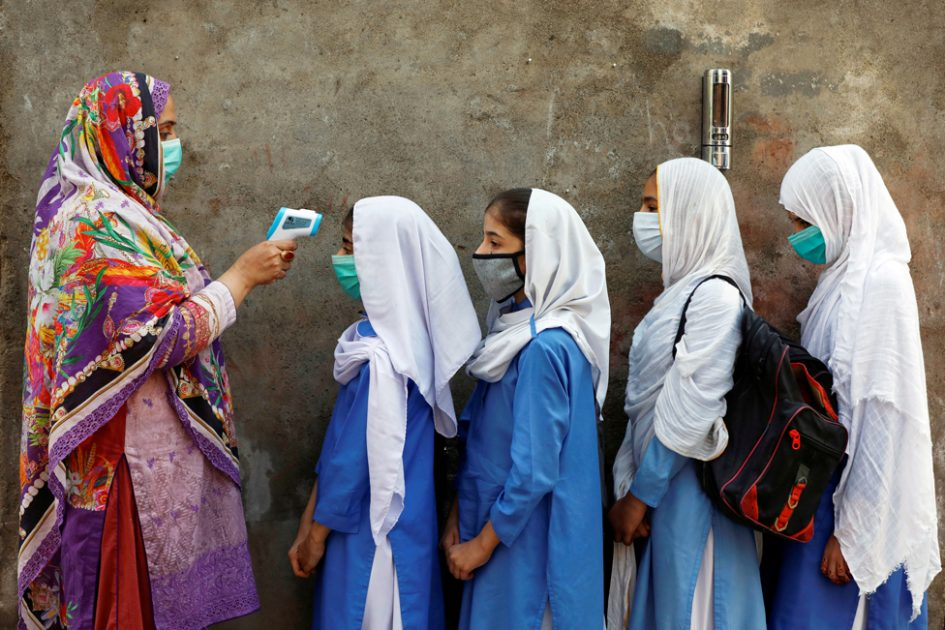 Students wear protective face masks as they have their temperature checked before entering a class in Peshawar, Pakistan 23 September 2020