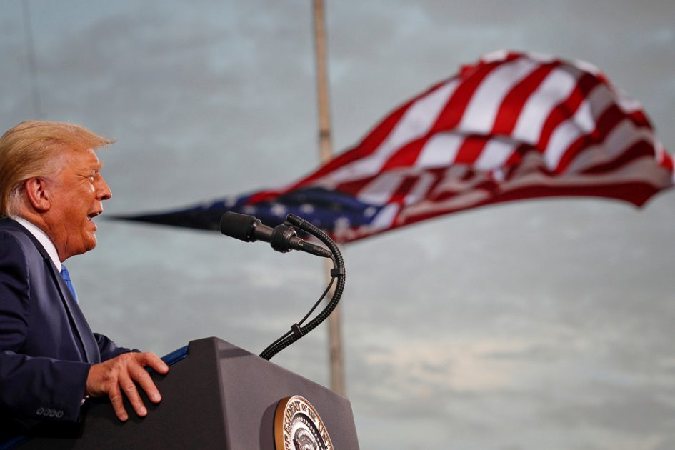 US President Donald Trump speaks, with a flag behind him, during a campaign rally at Cecil Airport in Jacksonville, Florida, on 24 September 2020