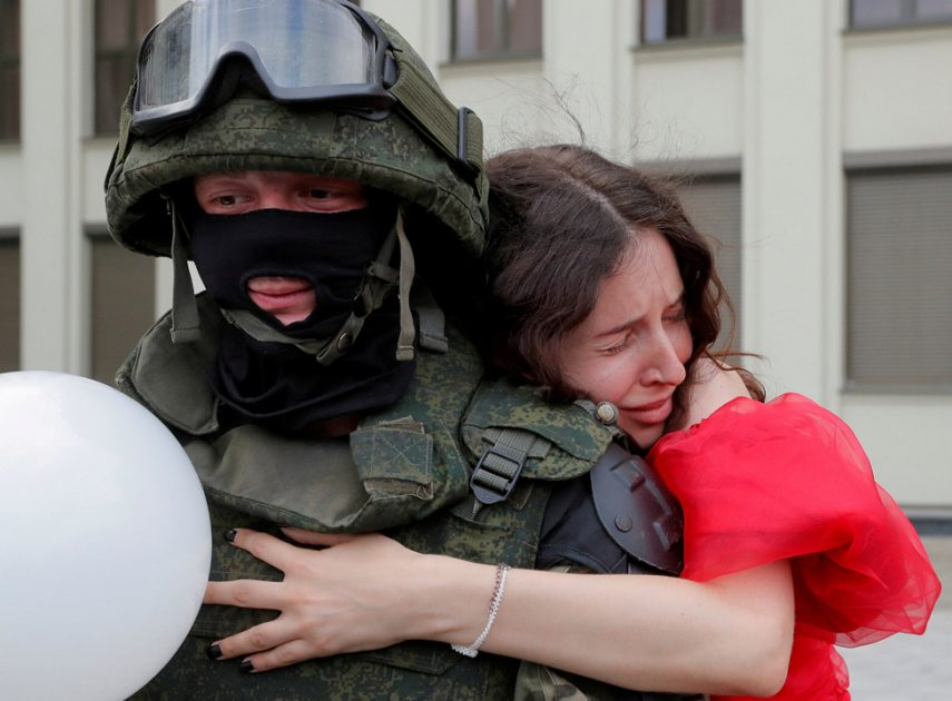 A woman embraces a member of the Belarusian interior troop near the Government House in Independence Square in Minsk, Belarus, 14 August 2020