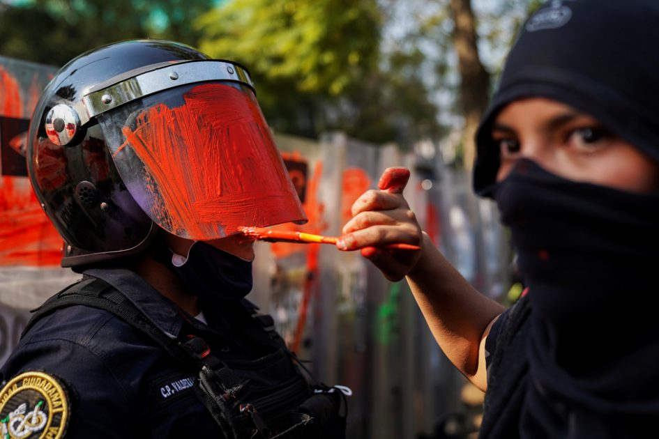 A demonstrator paints the helmet visor of a riot police officer, in Mexico City, Mexico, 11 November 2020