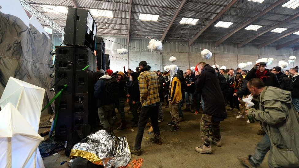 People stand in front of speakers inside the warehouse