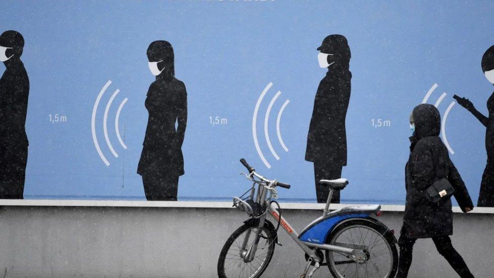 """Žena hoda pored plakata u Nemačkoj na kome piše """"Najbolji tim. Sa distance"""""""