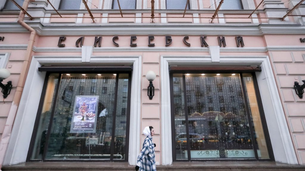 NOVEMBER 25, 2020: A woman walks past the Yeliseyevsky grocery store in Tverskaya Street, central Moscow