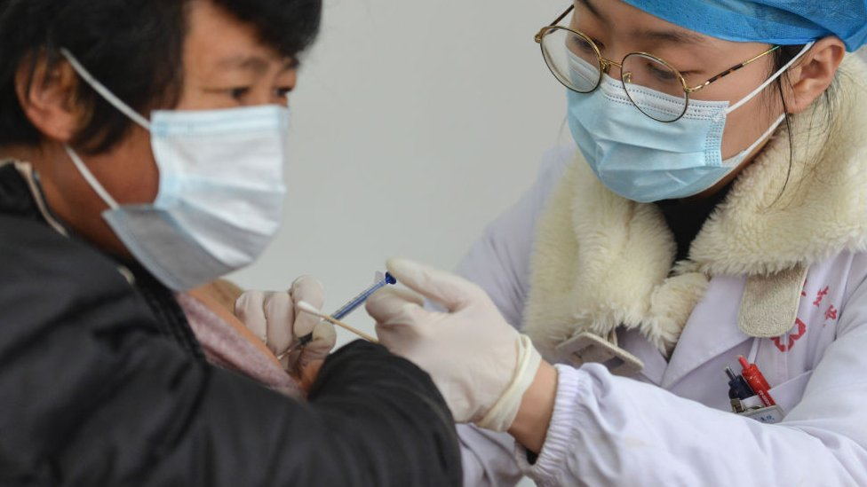 A medical worker vaccinates a rural resident at a COVID-19 vaccination site at the township level in Fuyang.