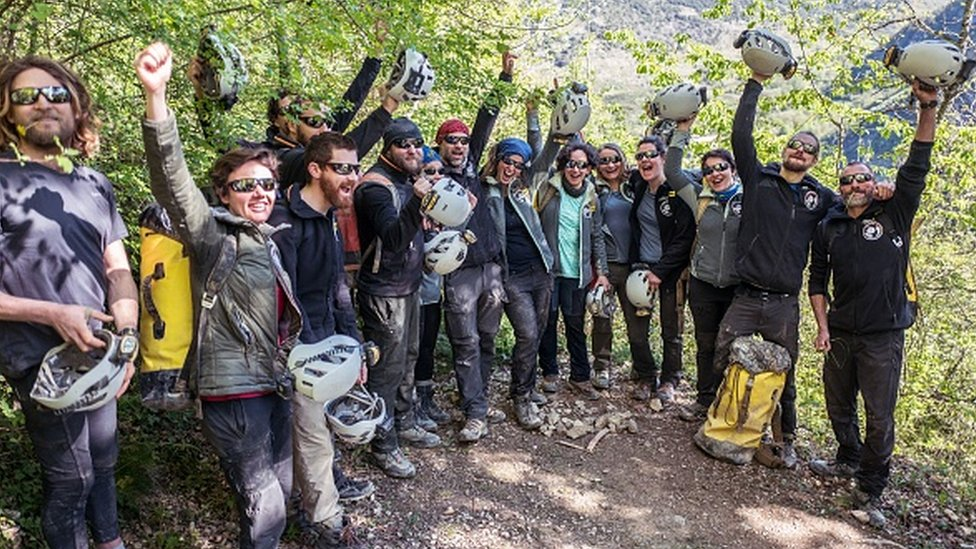 Volunteers celebrate after leaving the Lombrives cave