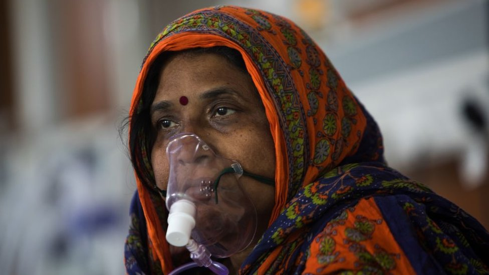 A COVID-19 coronavirus patient sits on her bed at the Intensive Care Unit of the Sharda Hospital, in Greater Noida