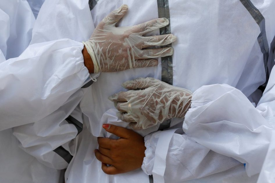 Relatives wearing personal protective equipment (PPE) mourn a man and place hands on each other's backs