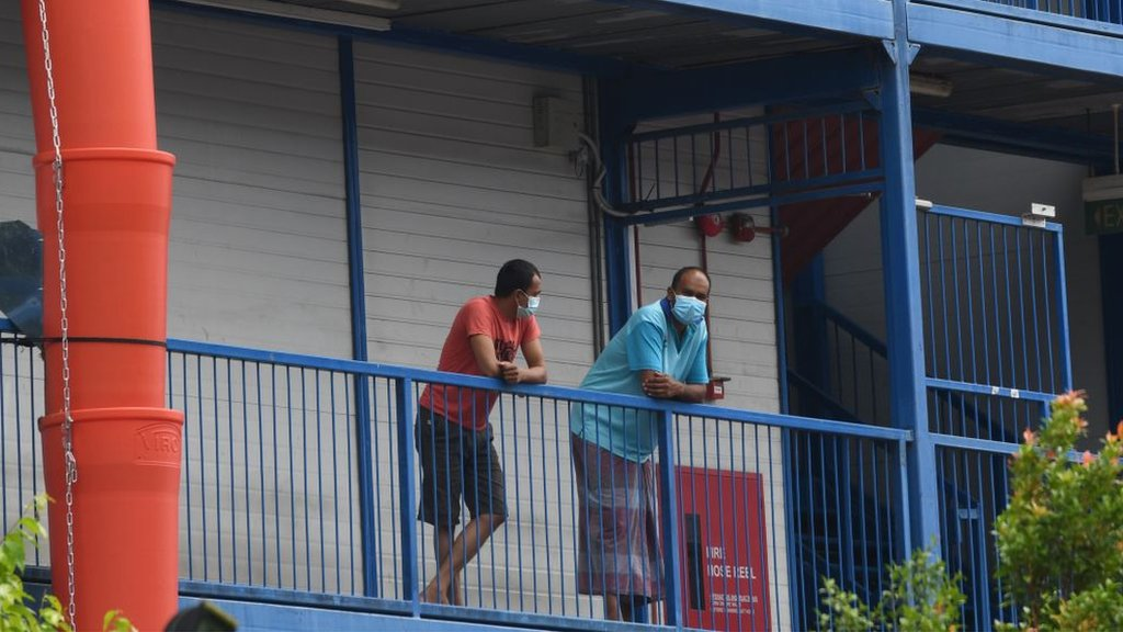 Migrant workers wearing face masks as prevention for the spread of the COVID-19 coronavirus look out from a quarantined dormitory building in Singapore on 20 May 2020.