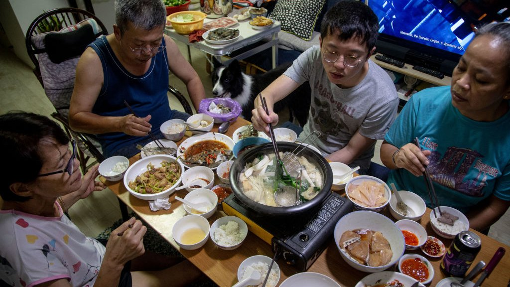 A family partakes in a steamboat meal for their reunion dinner at home on the eve of the lunar new year on 11 February 2021 in Singapore.