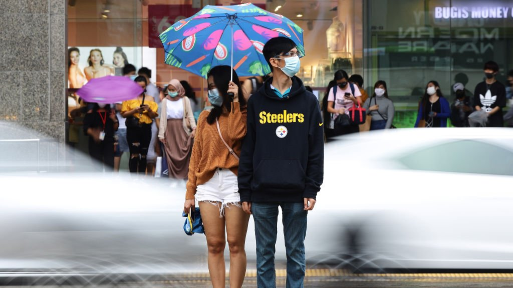 A couple wearing protective masks wait to cross a street in the rain on 10 January 2021 in Singapore
