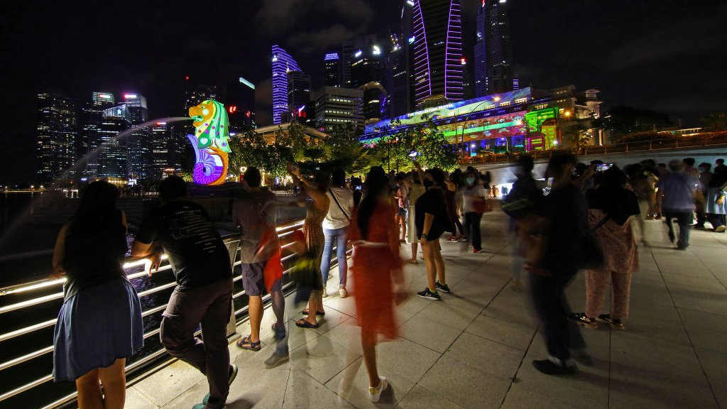 People watch light projection with illuminated artworks on the facade of the Merlion and the Fullerton Hotel at Marina Bay on 30 December 2020 in Singapore.