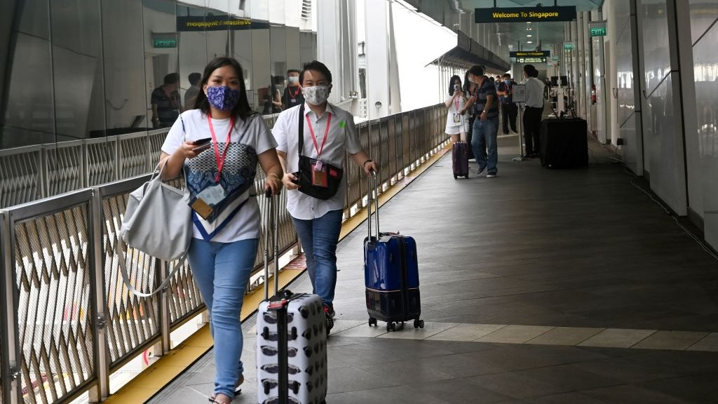 """Passengers walk toward the World Dream cruise ship docked at Marina Bay Cruise Centre before its departure to """"cruises to nowhere"""" in Singapore on November 6, 2020 in a bid to revive its pandemic-hit tourism industry."""