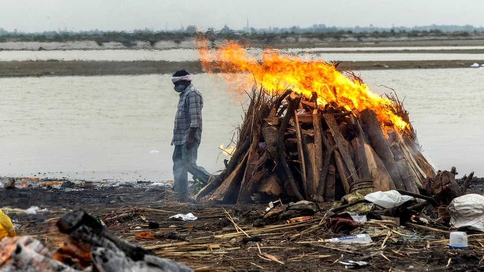 A man walks past burning pyres with people who died from the coronavirus disease (Covid-19), on the banks of the river Ganges in the northern state of Uttar Pradesh